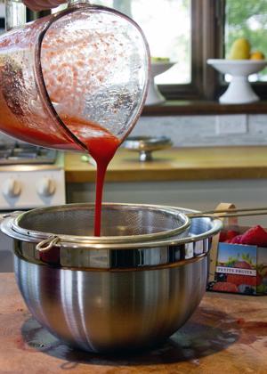 straining strawberry puree
