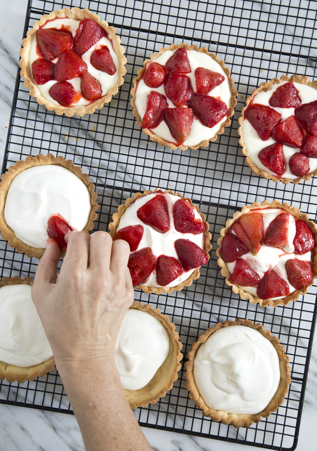 putting strawberries on tarts